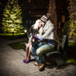 couple in love sitting on bench covering with plaid  — Stock Photo