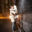 Young couple kissing at evening near black wall — Stock Photo