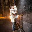 Young couple kissing at evening near black wall — Stock Photo #33633347