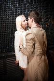 Man knuffelen sexy blonde vrouw in de buurt van zwarte muur — Stockfoto