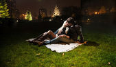 Night shot of couple in lying on grass — Stock Photo