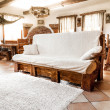 Big wooden sofa with white blanket — Stock Photo