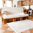 Wooden sofa standing in living room in country style — Stock Photo