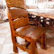 Big wooden chair standing behind dining table — Stock Photo