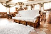 Big wooden sofa with white blanket — Stock Photo