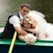 Newly married couple lying and hugging in rowing boat — Stock Photo