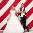 married couple posing against red striped wall — Lizenzfreies Foto