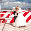 Bride and groom hugging in heliport against city view — Stock Photo
