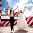 married couple holding hands while jumping on rooftop — ストック写真