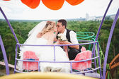 Married couple riding on Ferris wheel and kissing — Stock Photo