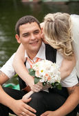 Bride kissing smiling groom on rowing boat — Stock Photo
