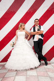Married couple posing against red striped wall — Stock Photo