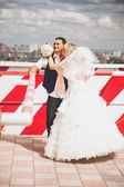 Bride kissing in cheek her groom while standing on rooftop — Stock Photo