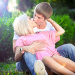 Muscular man hugging and kissing blonde woman on grass — 图库照片