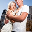 blonde woman hugging with muscular man against city — Stock Photo