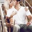 Sexy young couple kissing on metal stairs — Stock fotografie