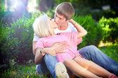 Homem musculoso, abraçando e beijando a mulher loira na grama — Fotografia Stock