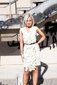 Girl in short white dress posing against metal construction — Stock Photo