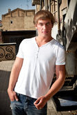 Tanned muscular man leaning against metal staircase — Stockfoto