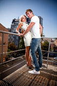 Young couple kissing on stairways against city view — Stock Photo