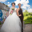 Bride standing in park with bridesmaid — Foto Stock