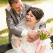 married couple laughing in park while sitting on bench — Stok fotoğraf