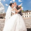 Married couple hugging against blue sky on square — Stock Photo #34097019