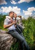 Men sitting on log in park and drinking beer after work — Stock Photo