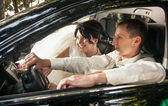 Groom driving car with bride sitting on passanger seat — Stock Photo