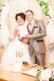 Bride and groom showing wedding document — Foto de Stock