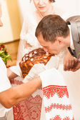 Handsome groom kissing loaf of bread by tradition — Stock Photo