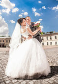 Married couple hugging against blue sky on square — Stock Photo