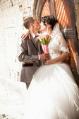 Groom hugging and kissing bride near old door — Stock Photo