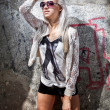 Sexy blonde girl in sunglasses against graffiti wall — Stock Photo