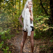 Blonde girl with long legs in white shirt posing in forest — Stock Photo