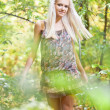 Blond girl in short dress posing in forest — Stock Photo