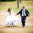 Bride and groom running and park — Stock Photo