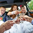 Married couple clinking glasses with friends in car — Stock Photo #34402997