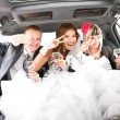 Couple having fun with friends in limousine — Stock Photo