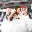 Couple having fun with friends in limousine — Zdjęcie stockowe