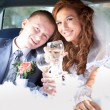 Bride and groom clinking glasses in limousine — Stock Photo