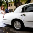 couple pushing white wedding limousine — Stock Photo