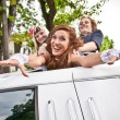 Stock Photo: Girls dragging bride in limousines hatch