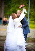 Bride with flowers hugging groom around neck — Stock Photo