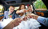 Married couple clinking glasses with friends in car — Stock Photo