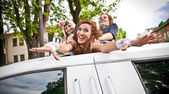 Girls dragging bride in limousines hatch — Stock Photo