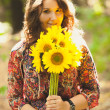 Brunette girl holding bunch of sunflowers in park — Stock Photo