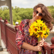 Brunette girl in sunglasses holding sunflowers on bridge — Stock Photo