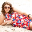 Girl in sunglasses and dress lying on beach — Stock Photo