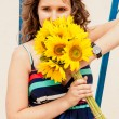 Portrait of brunette young woman holding bunch of yellow flowers — ストック写真